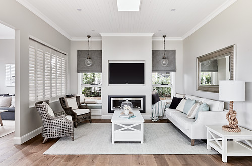 Couch, coffee table, fireplace and designer armchair in pale, elegant living room