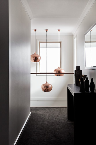 Vases on console table and pendant lamps in stairwell