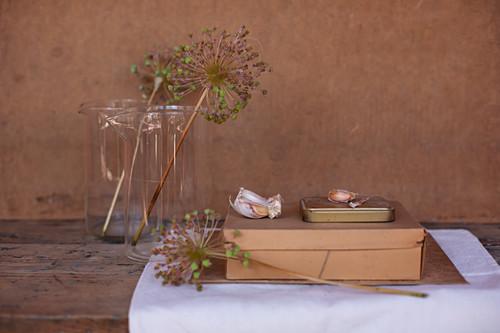 Dried garlic flowers in glass jars, cardboard box, tin and garlic cloves