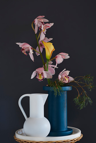 Vase of boat orchids, calla lily and pine branch