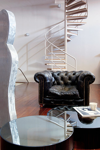 Leather armchair and coffee table in front of spiral staircase in living room