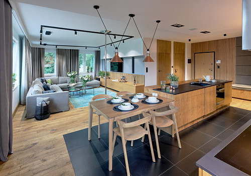 Kitchen counter with bar stools and breakfast table at one end and elegant lounge in background in open-plan interior