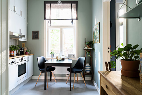 Table and two chairs below window in kitchen with houseplant on wooden table in foreground