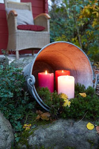Three pillar candles in zinc bucket lying on side in garden