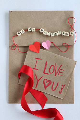 Love note on craft paper and string of lettered beads