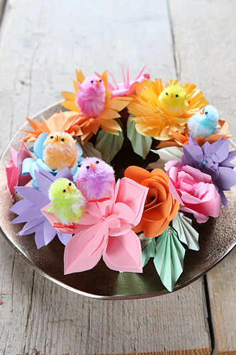 Chick decorations on wreath of colourful paper flowers