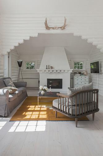 Sessel mit grauem Polster, passendes Sofa und Couchtisch vor Kamin in weiß gestrichenem Blockhaus