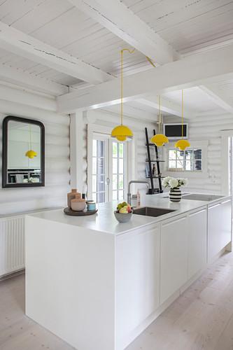 Weiße Kücheninsel in weiß gestrichenem Blockhaus