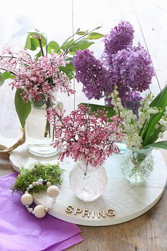Flieder, Zwergflieder und Maiglöckchen in verschiedenen Vasen