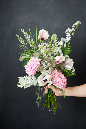 Hand holding early summer bouquet in pastel shades