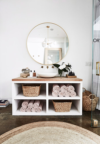 Vanity with counter basin, baskets and towels, round mirror on the wall
