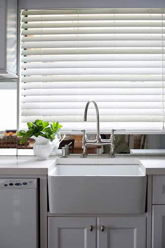 Kitchen counter with sink below window with closed louvre blinds