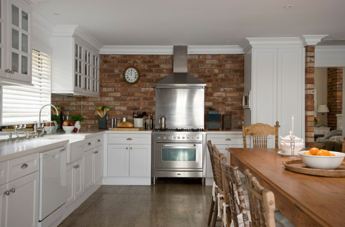 Kitchen with white cabinets, stainless steel cooker against brick wall and solid wooden dining table