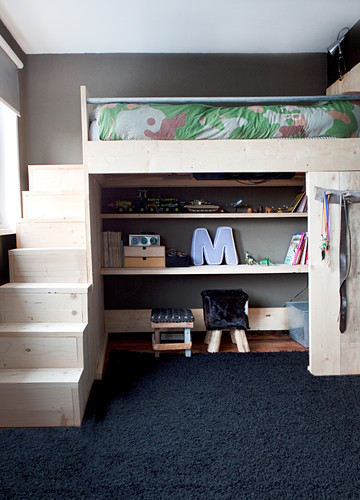 Loft bed with pale wooden steps and shelves below in child's bedroom