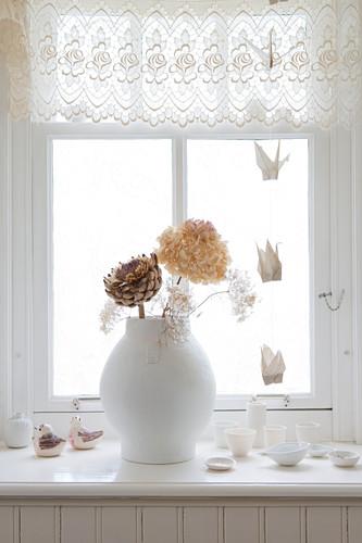 Vase mit getrockneten Blüten auf Fensterbank