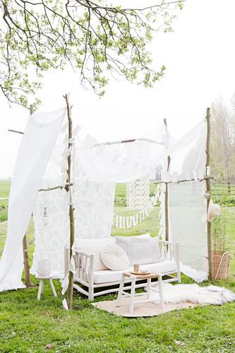 Sofa im DIY-Gartenpavillon aus Ästen und weißem Vorhang