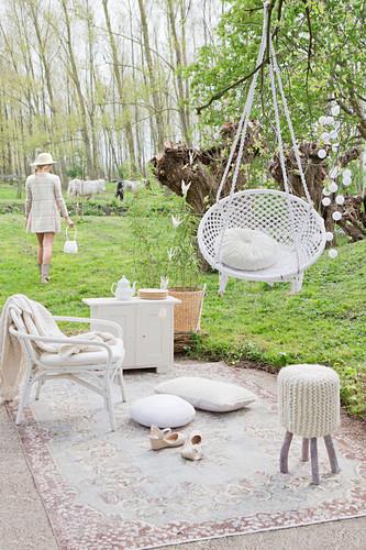 Idyllischer Gartenplatz mit Hängesessel, Kissen, Hocker und Rattansessel auf Teppich