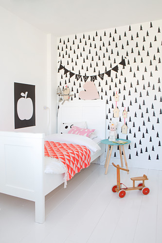 White bed and black-and-white wallpaper in Scandinavian-style child's bedroom