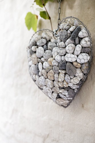 Wire heart filled with pebbles on wall