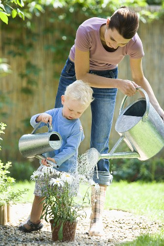 A mother and son watering the flowers in a garden