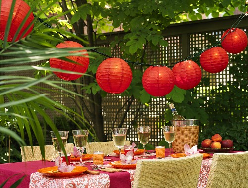 Festive table with white wine & Chinese lanterns out of doors