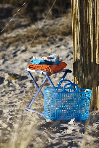 A blue plastic basket next to a stool with towel on a sandy beach