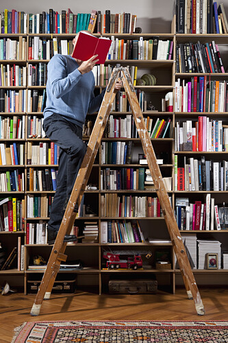 A man reading on a ladder in a home library