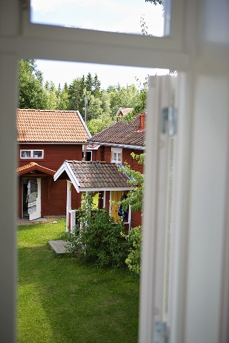 A view through a window of a wooden house with a porch