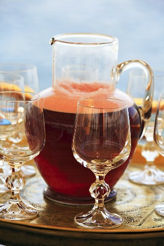 A refreshing red drink in a carafe with glass stemware on a tray, Egypt
