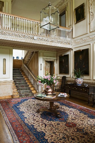 A hallway in a Baroque-style castle with a round wooden table on an Oriental rug in front of a flight of stairs with a gallery