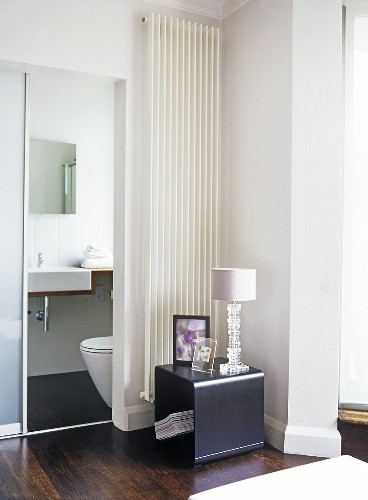 A modern, minimalist bedroom decorated in neutral colour, view through sliding door to ensuite bathroom, washbasin, toilet, wooden floor, wall mounted radiator, table, lamp,