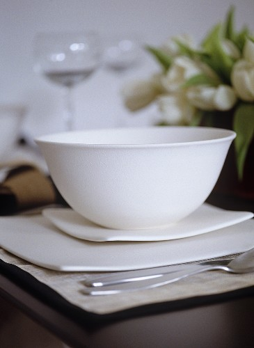 Close up of white ceramic bowl on modern square dishes, place mat, cutlery, flowers, wine glasses,, Interiors, dining, detail, tableware, modern, simple, elegant, stylish,