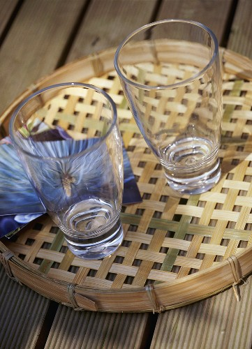 A detail of two glasses on a bamboo tray set on a wooden table,