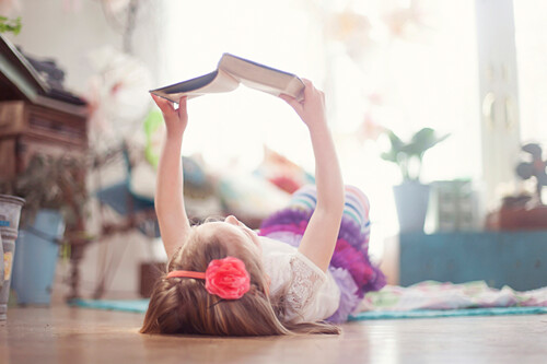Girl reading book on living room floor
