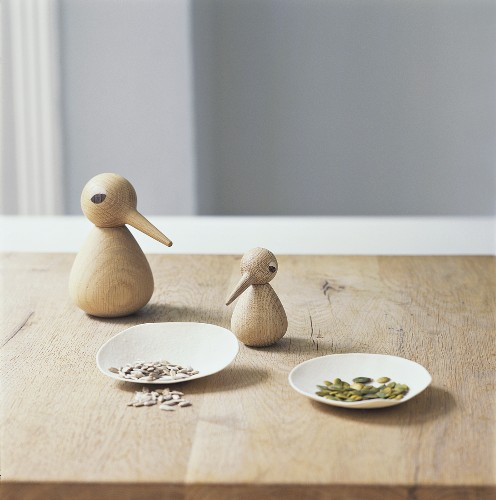 Two wooden birds, sunflower seed and pumpkin seeds on a table