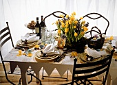 A festively laid Easter table in a country house style decorated with spring flowers