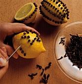 Making a lemon pomander with cloves