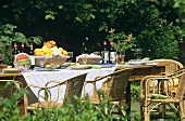 Laid table with wine and fruit in garden with cane chairs