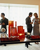 Decorative red glass vases and gerberas on a tray arranged on a table with party guests in the background