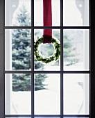 Weihnachtskranz aus Eis und Zweigen an einer Glastür