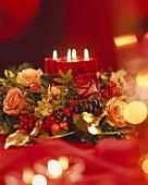 Adventsgesteck mit Rosen, Goldfäden und brennenden Kerzen