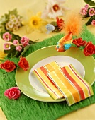 Place-setting with napkins, bird on artificial grass table mat