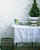 Table with small Christmas tree and pile of plates