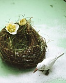 Grass bird's nest with white wooden bird