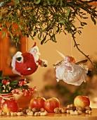 Two jolly Christmas tree ornaments on a mistletoe branch