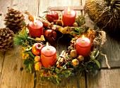 Rustikaler Adventskranz mit brennenden Kerzen