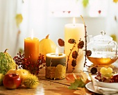 Autumn or winter table decoration with candles, tea, etc.