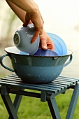 Washing crockery in blue bowl on camping stool