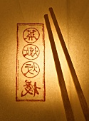 Wooden chopsticks on paper with Asian characters