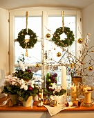 White Christmas window decoration with candles, plants etc.